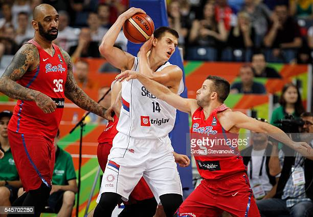 Nikola Jokic of Serbia is challenged by JJ Barea and Peter Ramos of Puerto Rico during the 2016 FIBA World Olympic Qualifying basketball Final match...