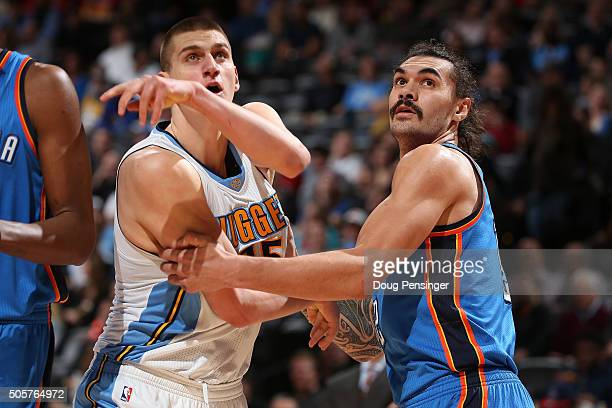 Nikola Jokic of the Denver Nuggets and Steven Adams of the Oklahoma City Thunder battle for rebounding position at Pepsi Center on January 19 2016 in...