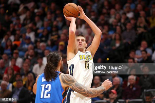 Nikola Jokic of the Denver Nuggets puts up a shot over Steven Adams of the Oklahoma City Thunder at the Pepsi Center on November 9 2017 in Denver...