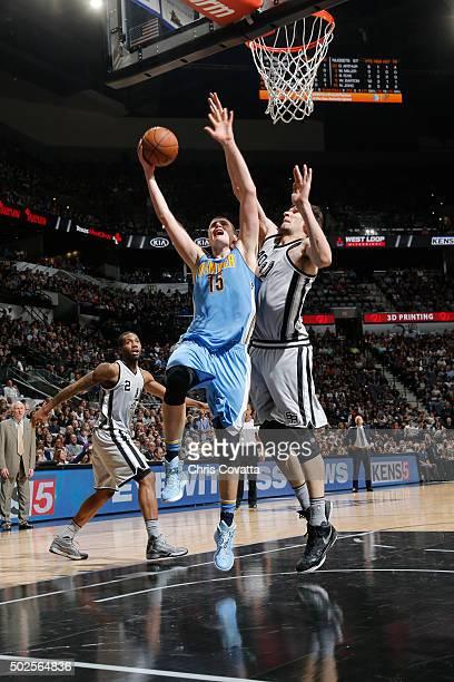 Nikola Jokic of the Denver Nuggets shoots the ball against Boban Marjanovic of the San Antonio Spurs on December 26 2015 at the ATT Center in San...