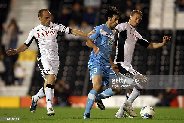 Nikola Kalinic of FC Dnipro is closed down by Danny Murphy and Brede Hangeland of Fulham during the UEFA Europa League PlayOff round qualifying first...