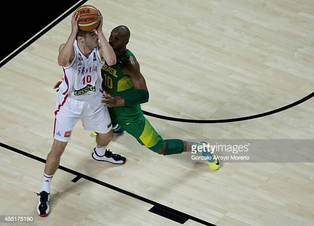 Nikola Kalinic of Serbia drives against Leandrinho Barbosa of Brazil during the 2014 FIBA World Basketball Championship quarter final match between...