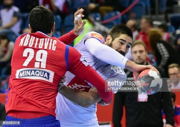 TOPSHOT Nikola Karabati of France fights for the ball with Ilija Abutovi of Serbia during the Men's 2016 EHF European Handball Championships match...