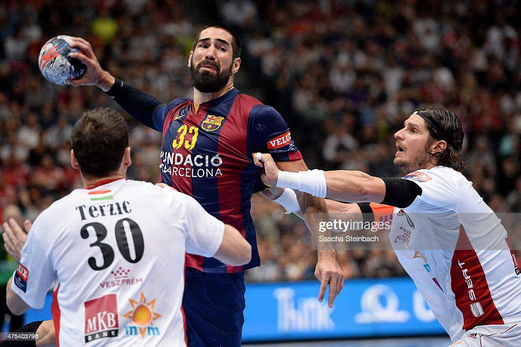Nikola Karabatic of Barcelona (C) is challenged by Mirsad Terzic (L) and Laszlo Nagy (R) of Veszprem during the 'VELUX EHF FINAL4' final match between FC Barcelona and MKB-MVM Veszprem at Lanxess Arena on May 31, 2015 in Cologne, Germany.
