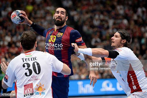 Nikola Karabatic of Barcelona is challenged by Mirsad Terzic and Laszlo Nagy of Veszprem during the 'VELUX EHF FINAL4' final match between FC...