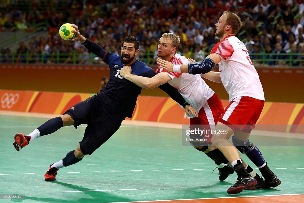 Nikola Karabatic of France controls the ball against Rene Toft Hansen and Henrik Toft Hansen of Denmark during the Men's Gold Medal Match between...
