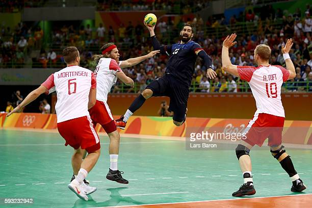 Nikola Karabatic of France jumps to shoot against Mikkel Hansen Rene Toft Hansen and Casper Mortensen of Denmark during the Men's Gold Medal Match...