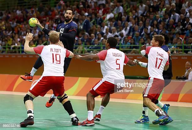 Nikola Karabatic of France jumps to throw against Rene Toft Hansen Mads Mensah Larsen and Lasse Svan of Denmark during the Men's Gold Medal Match...