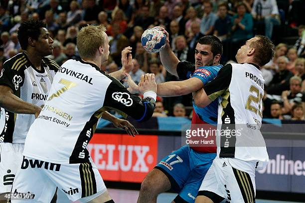 Nikola Markoski of Metalurg challenges for the ball with Christian Zeitz of Kiel during the Velux EHF Champions League quarter final handball match...