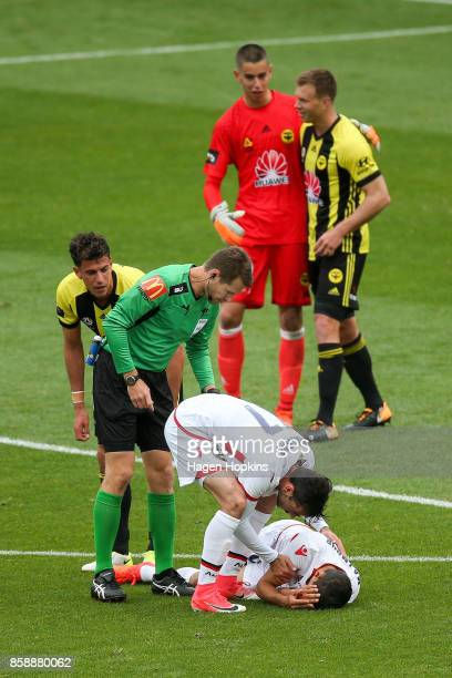 Nikola Mileusnic of Adelaide United checks on the health of teammate Karim Matmour during the round one ALeague match between Wellington Phoenix and...