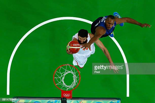 Nikola Mirotic of Spain goes to the basket under pressure against Boris Diaw of France during the Men's Quarterfinal match on Day 12 of the Rio 2016...