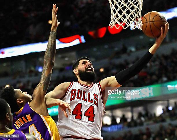 Nikola Mirotic of the Chicago Bulls drives past Brandon Ingram of the Los Angeles Lakers at the United Center on November 30 2016 in Chicago Illinois...