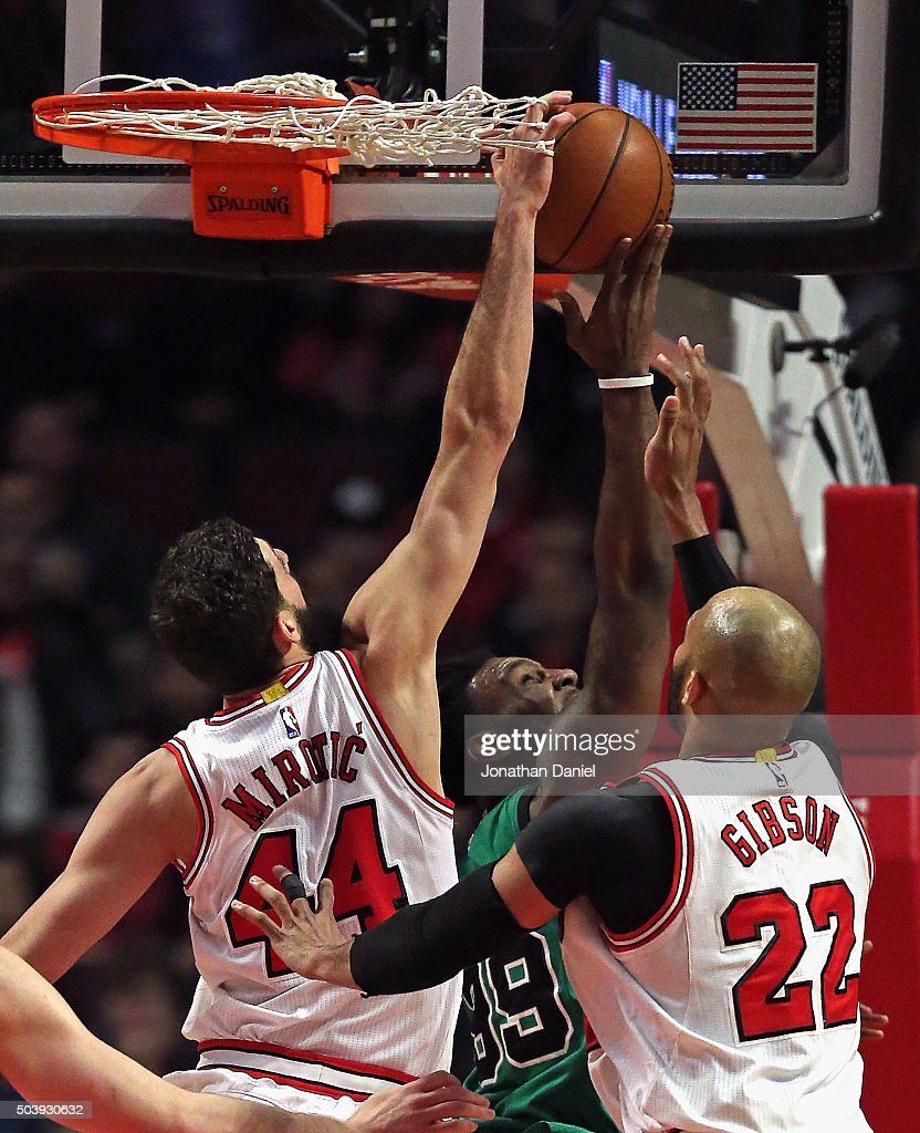 Nikola Mirotic of the Chicago Bulls gets his hand caught in the net while trying to block a shot by Jae Crowder of the Boston Celtics as Taj Gibson...