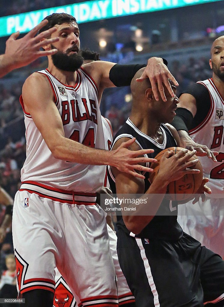 Nikola Mirotic #44 of the Chicago Bulls grabs <a gi-track='captionPersonalityLinkClicked' href=/galleries/search?phrase=Jarrett+Jack&family=editorial&specificpeople=208109 ng-click='$event.stopPropagation()'>Jarrett Jack</a> #2 of the Brooklyn Nets during a rebound at the United Center on December 21, 2015 in Chicago, Illinois.