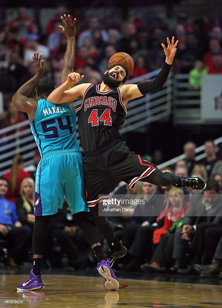 Nikola Mirotic #44 of the Chicago Bulls is fouled by Jason Maxiell #54 of the Charlotte Hornets at the United Center on March 23, 2015 in Chicago, Illinois.