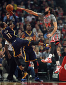 Nikola Mirotic of the Chicago Bulls tries to block a shot by Monta Ellis of the Indiana Pacers at the United Center on November 16 2015 in Chicago...