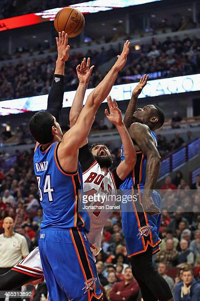 Nikola Mirotic of the Chicago Bulls tries to get off a shot between Enes Kanter and Anthony Morrow of the Oklahoma City Thunder at the United Center...
