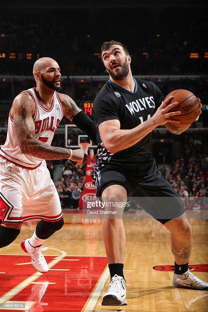 Nikola Pekovic #14 of the Minnesota Timberwolves drives against Carlos Boozer #5 of the Chicago Bulls on January 27, 2014 at the United Center in Chicago, Illinois.