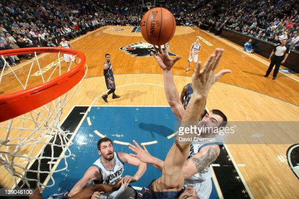 Nikola Pekovic of the Minnesota Timberwolves goes to the basket as teammate Kevin Love looks on during the game against the Charlotte Bobcats on...
