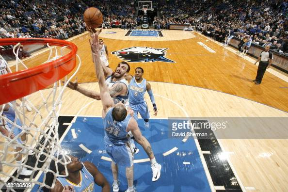 Nikola Pekovic of the Minnesota Timberwolves goes to the basket against Kosta Koufos of the Denver Nuggets during the game between the Minnesota...