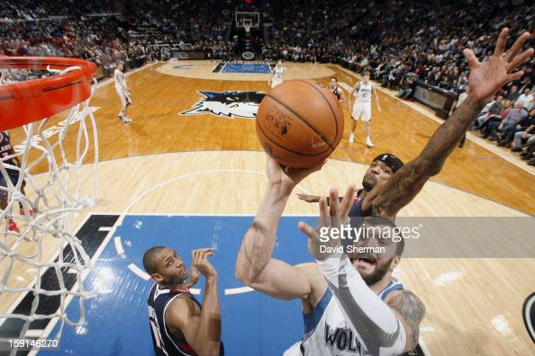 Nikola Pekovic of the Minnesota Timberwolves goes up for the shot while Josh Smith of the Atlanta Hawks attempts to block his shot during the game on...