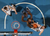 Nikola Pekovic of the Minnesota Timberwolves watches teammate Kevin Love reach for the ball against DeSagana Diop and Tyrus Thomas of the Charlotte...