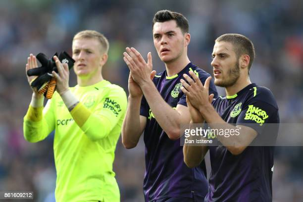 Nikola Vlasic Michael Keane and Jordan Pickford of Everton appalud the away fans after the Premier League match between Brighton and Hove Albion and...