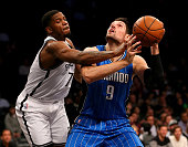 Nikola Vucevic of the Orlando Magic heads for the net as Joe Johnson of the Brooklyn Nets defends at Barclays Center on December 14 2015 in the...