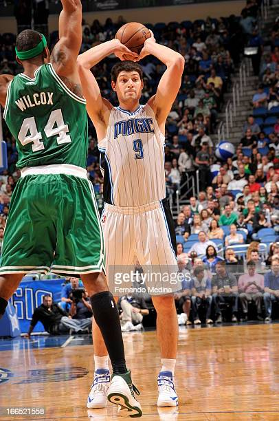 Nikola Vucevic of the Orlando Magic looks to pass the ball against Chris Wilcox of the Boston Celtics during the game on April 13 2013 at Amway...