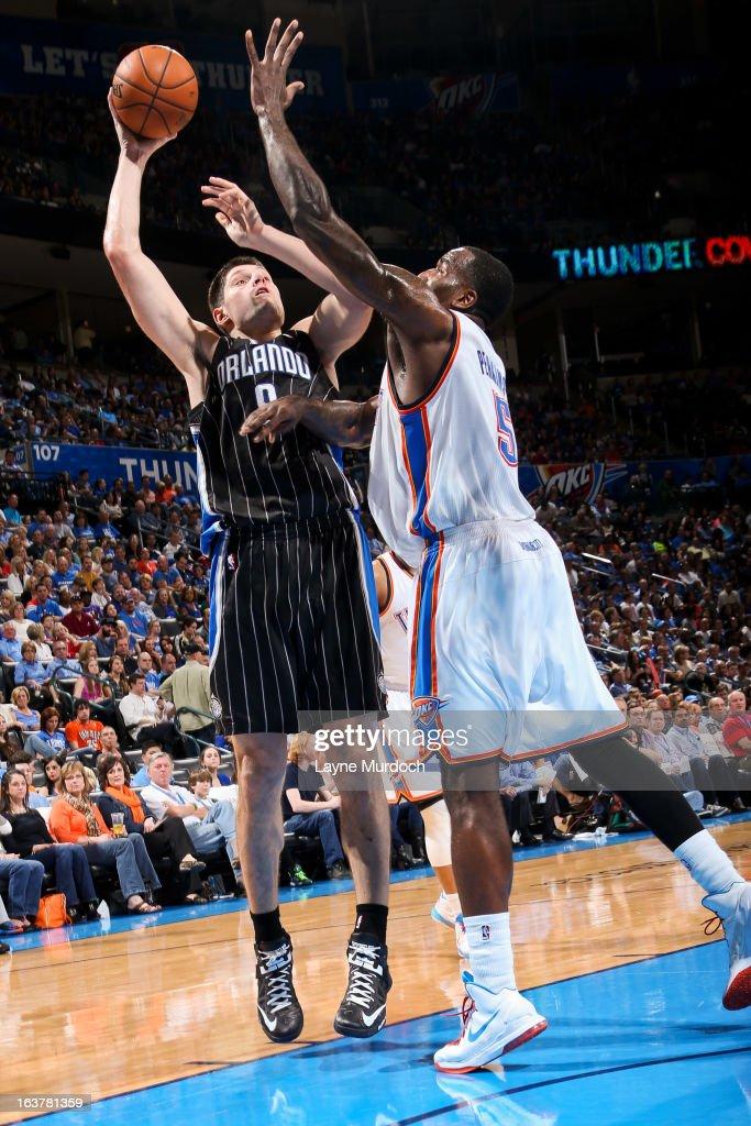 Nikola Vucevic #9 of the Orlando Magic shoots against Kendrick Perkins #5 of the Oklahoma City Thunder on March 15, 2013 at the Chesapeake Energy Arena in Oklahoma City, Oklahoma.