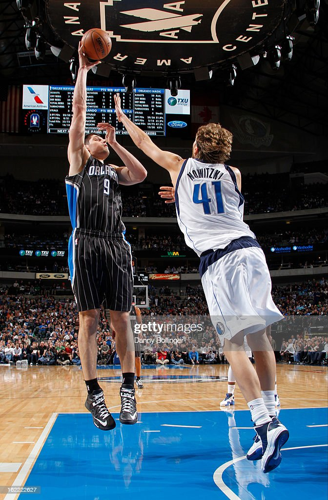 Nikola Vucevic #9 of the Orlando Magic shoots the ball against Dirk Nowitzki #41 of the Dallas Mavericks on February 20, 2013 at the American Airlines Center in Dallas, Texas.
