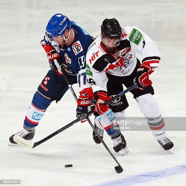 Nikolai Goc of Mannheim is challenged by Evan Rankin of Koeln during the DEL match between Adler Mannheim and Koelner Haie at SAP Arena on December...