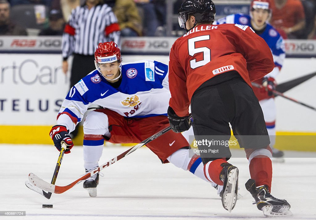 Nikolai Goldobin #11 of Russia battles for the puck against Mirco Muller #5 of Switzerland during the 2015 IIHF World Junior Championship on December 28, 2014 at the Air Canada Centre in Toronto, Ontario, Canada.
