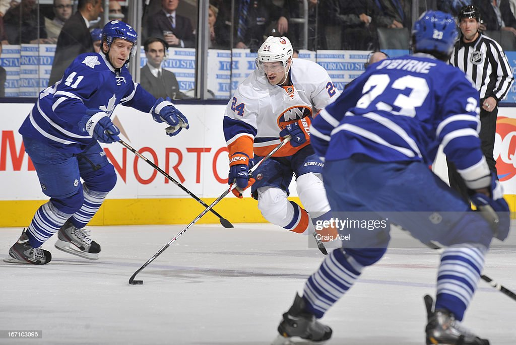 Nikolai Kulemin #41 and Ryan O'Byrne #23 of the Toronto Maple Leafs defend as Brad Boyes #24 of the New York Islanders skates with the puck during NHL game action April 18, 2013 at the Air Canada Centre in Toronto, Ontario, Canada.