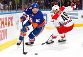Nikolai Kulemin of the New York Islanders battles for possesion with Victor Rask of the Carolina Hurricanes at Nassau Veterans Memorial Coliseum on...