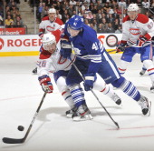Nikolai Kulemin of the Toronto Maple Leafs battles for the puck with Josh Gorges of the Montreal Canadiens during NHL game action October 6 2011 at...