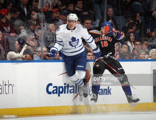 Nikolai Kulemin of the Toronto Maple Leafs escapes a hit by Micheal Haley of the New York Islanders at the Nassau Veterans Memorial Coliseum on...