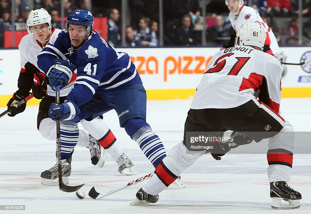 Nikolai Kulemin #41 of the Toronto Maple Leafs fishes for the puck in front of Andre Benoit #61 of the Ottawa Senators during NHL action at the Air Canada Centre February 16, 2013 in Toronto, Ontario, Canada.