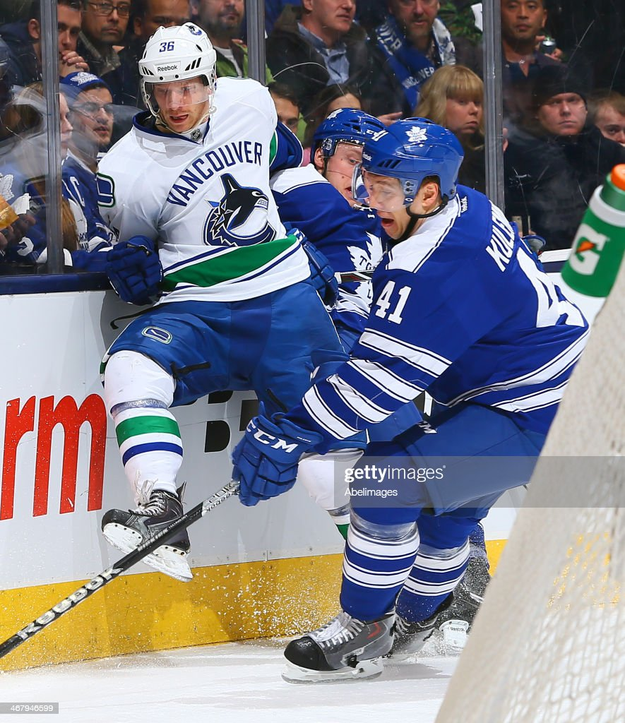 Nikolai Kulemin #41 of the Toronto Maple Leafs gets away from Jannik Hansen #36 of the Vancouver Canucks during NHL action at the Air Canada Centre February 8, 2014 in Toronto, Ontario, Canada.