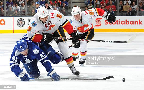 Nikolai Kulemin of the Toronto Maple Leafs is checked by Mark Giordano of the Calgary Flames during NHL game action October 15 2011 at Air Canada...