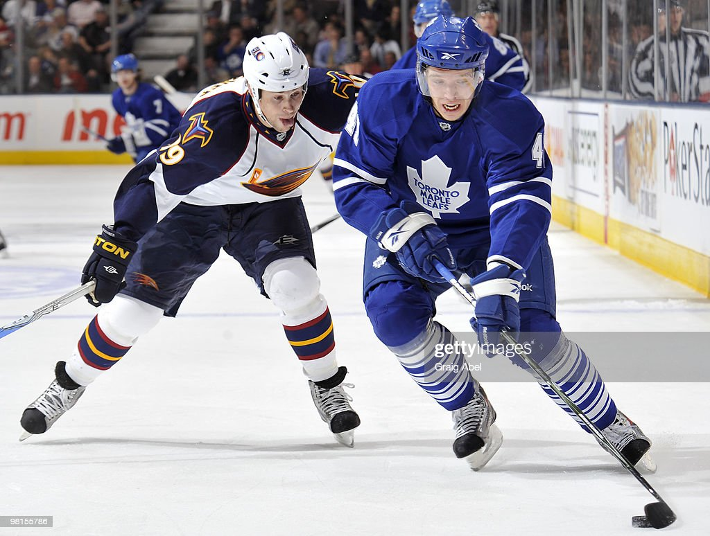 Nikolai Kulemin of the Toronto Maple Leafs skates the puck away from Marty Reasoner of the Atlanta Thrashers March 30 2010 at the Air Canada Centre...