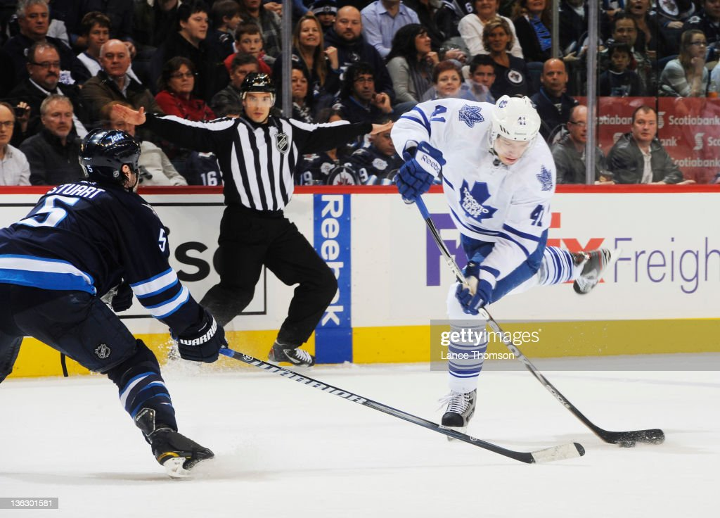<a gi-track='captionPersonalityLinkClicked' href=/galleries/search?phrase=Nikolai+Kulemin&family=editorial&specificpeople=537949 ng-click='$event.stopPropagation()'>Nikolai Kulemin</a> #41 of the Toronto Maple Leafs takes a shot as Mark Stuart #5 of the Winnipeg Jets defends during third period action at the MTS Centre on December 31, 2011 in Winnipeg, Manitoba, Canada.