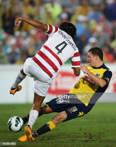 Nikolai ToporStanley of the Wanderers defends against Mitchell Duke of the Mariners during the round 23 ALeague match between the Central Coast...
