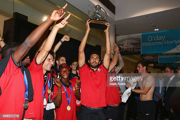 Nikolai ToporStanley of the Western Sydney Wanderers hold aloft the trophy as the team arrives at Sydney International Airport from Saudi Arabia...