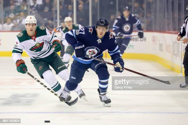 Nikolaj Ehlers of the Winnipeg Jets and Mike Reilly of the Minnesota Wild chase the loose puck down the ice during first period action at the Bell...