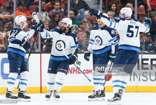 Nikolaj Ehlers of the Winnipeg Jets celebrates his second firstperiod goal with Mathieu Perreault Joel Armia and Tyler Myers during the game against...