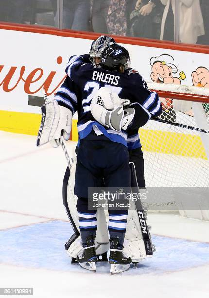 Nikolaj Ehlers of the Winnipeg Jets embraces goaltender Connor Hellebuyck following a 21 victory over the Carolina Hurricanes at the Bell MTS Place...