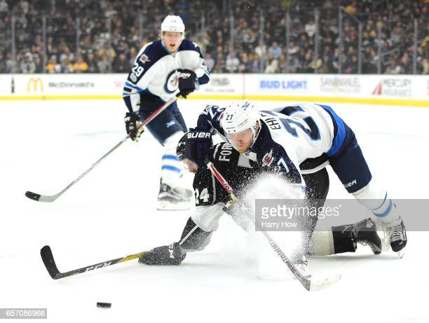 Nikolaj Ehlers of the Winnipeg Jets falls over Derek Forbort of the Los Angeles Kings as Patrik Laine look for a pass during the first period at...