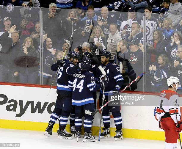 Nikolaj Ehlers of the Winnipeg Jets gets congratulated by teammates Blake Wheeler Josh Morrissey and Dustin Byfuglien after scoring a third period...