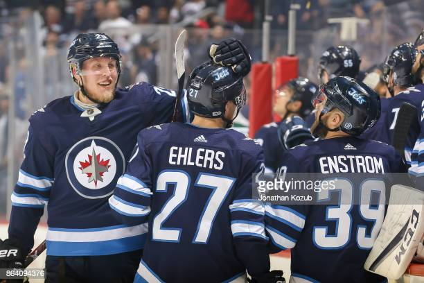 Nikolaj Ehlers of the Winnipeg Jets gets congratulated by teammates Patrik Laine and Toby Enstrom after scoring a first period goal against the...